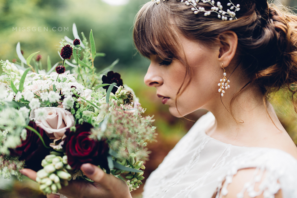 Close up of Bride's face with wild forest bouquet, wearing Kelly Spence earings and pearl crown and dress by Faith Caton Barber. Woodland elopement inspiration by Miss Gen Photography, London and destination creative reportage wedding photographer.