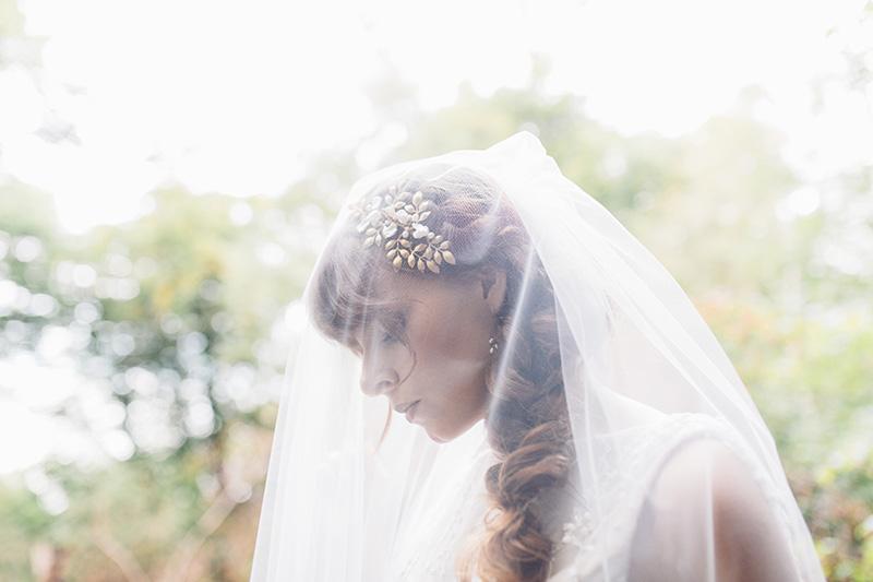 bride wearing veil in the woods