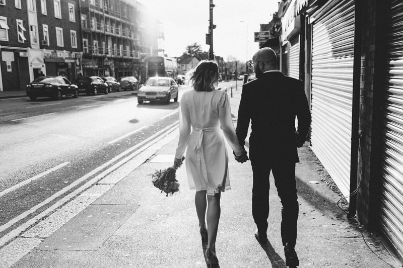 natural relaxed wedding photo of bride and groom walking down East London street by Miss Gen