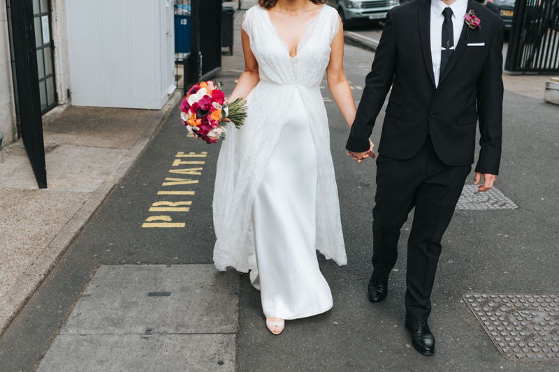 bride and groom walking down street in london by alternative modern wedding photographer miss gen
