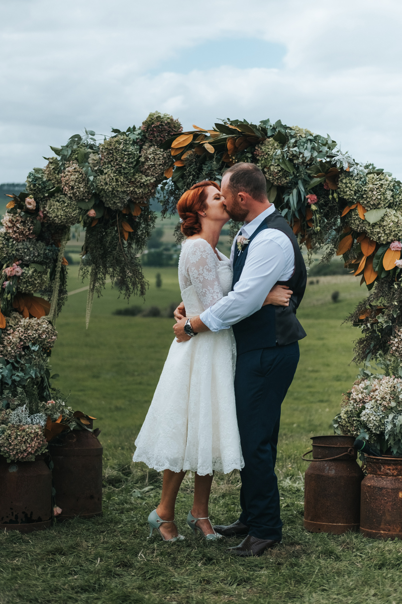 couple getting married under floral arch in countryside of new zealand by destination wedding photogrpaher miss gen