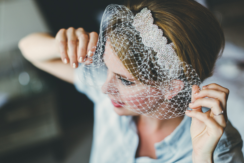 Bridal preparations putting on birdcage veil