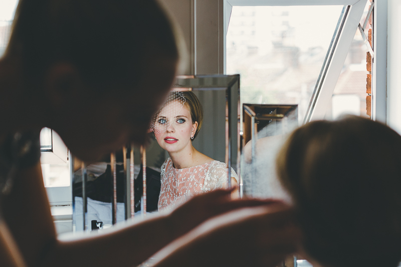Bridal preparations beautiful bride reflected in mirror red lips, peach wedding dress, birdcage veil