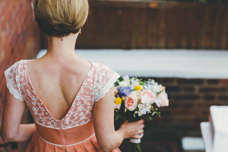 Bride walking down stairs from behind, wearing peach wedding dress with bouquet of flowers