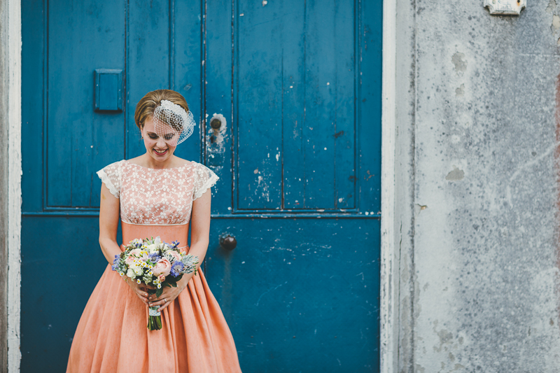 Bride standing in front of old textured blue painted door, wearing peach wedding dress and a birdcage veil with bouquet of flowers