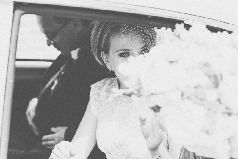 Bride getting into wedding car with lovely bouquet of flowers