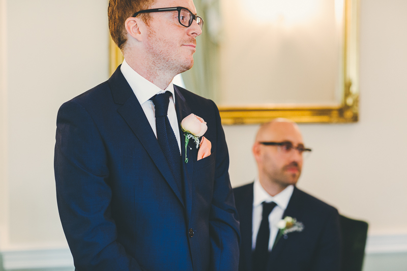 Groom wearing blue suit waiting in Portsmouth Registry Office