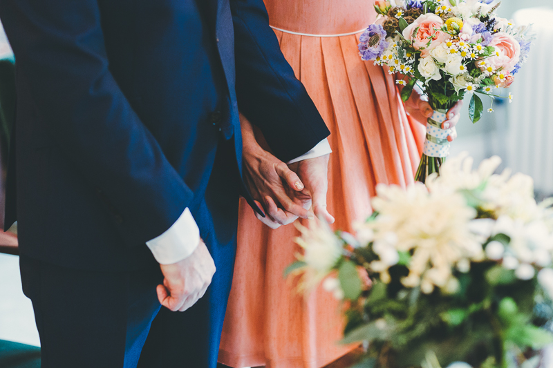 Bride and groom holding hands during the wedding ceremony at Portsmouth Registry Office