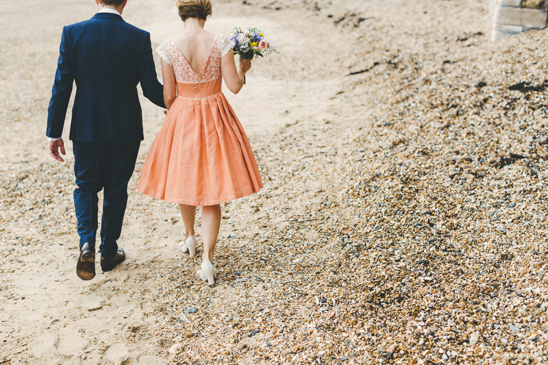 Natural wedding photos of Bride and groom in Old Portsmouth, bride wears peach, coral coloured wedding dress with cream beaded shoes and bouquet. Groom wears blue suit. Photos on the beach.