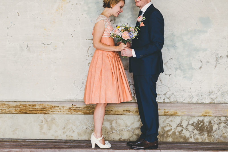 Natural wedding photos of Bride and groom in Old Portsmouth, bride wears peach, coral coloured wedding dress with cream beaded shoes and bouquet. Groom wears blue suit.