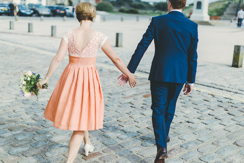 Bride and groom walking down the street in Old Portsmouth, form behind, bride wears peach, coral coloured wedding dress with cream beaded shoes and bouquet. Groom wears blue suit.