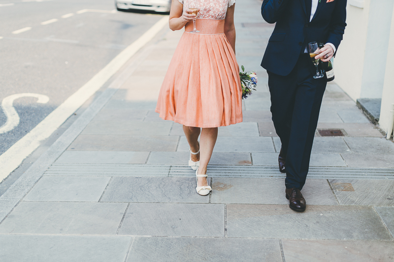 Bride and groom walking down the street in Old Portsmouth, bride wears peach, coral coloured wedding dress with cream beaded shoes and bouquet. Groom wears blue suit.