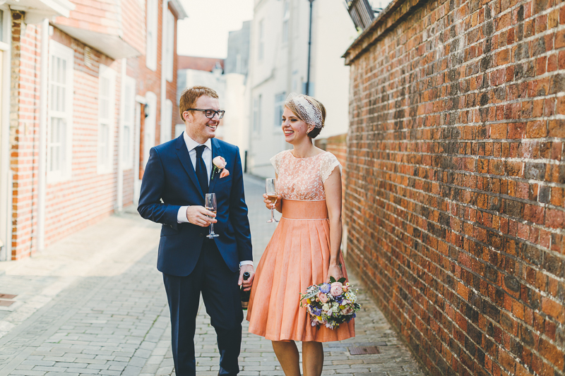Bride and groom walking down the street in Old Portsmouth, bride wears peach, coral coloured wedding dress with cream beaded shoes and bouquet. Groom wears blue suit. Drinking champagne.