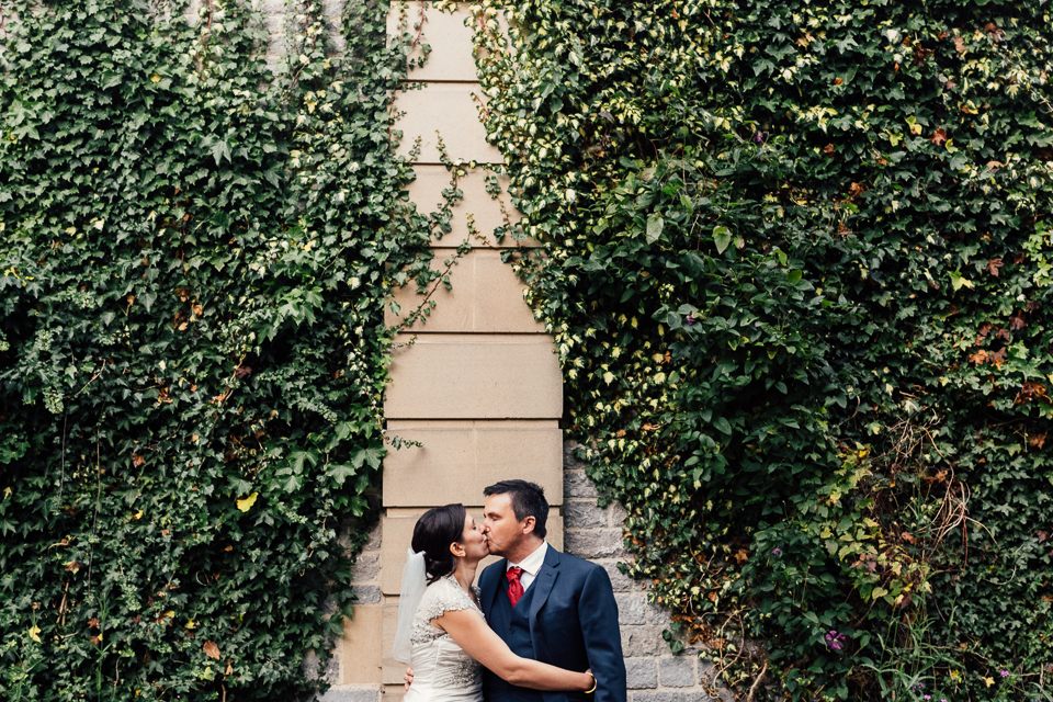 Bride and groom kissing against a brick wall covered in ivy at Thornbridge Hall in Derbyshire, Peak District. Creative, contemporary, alternative, natural wedding photography at Thornbridge Hall in the Peak District - Miss Gen Photography, London and destination wedding photographer.