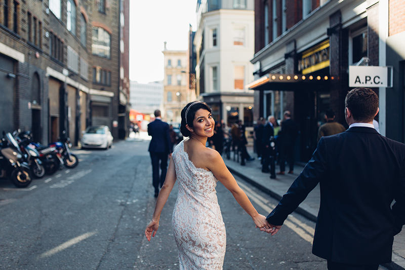 Bride looking over shoulder walking down the street in Shoreditch outside The Boundary. Bride wears a one shoulder slinky lace dress and beaded headband.
