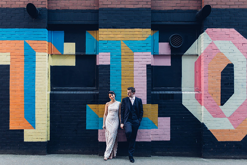 Contemporary Bride & Groom standing in front of street art in Shoreditch