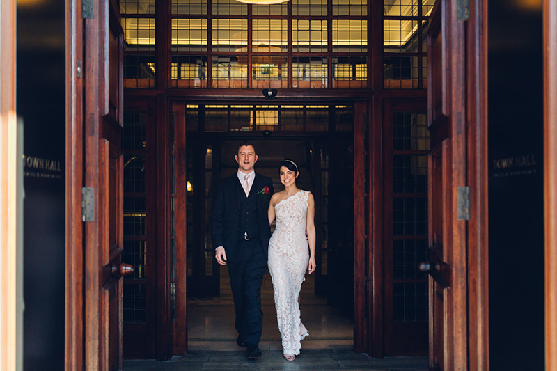 Modern bride & groom walking out of the Town Hall Hotel in Bethnal Green. Bride wears a slinky lace one shoulder dress.