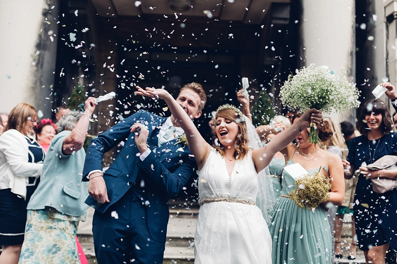 bride and groom with confetti outside stoke newington town hall by miss gen