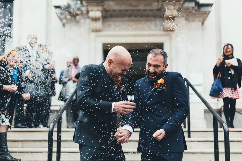 Two grooms covered with Confetti on steps of Islington Town Hall by Miss Gen, London wedding photographer