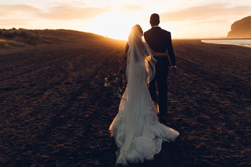 Bride And Groom Walking Into The Sunset On Bethells Beach New Zealand By Destination Wedding Photographer