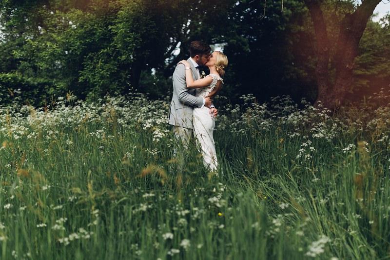 Bride and groom in wildflower meadow by destination wedding photographer miss gen