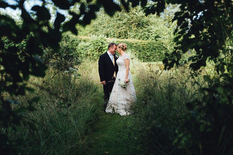 bride and groom in field in england by destination wedding photographer missgen