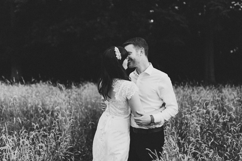 black and white image of natural bride and groom embrace in field by miss gen, london wedding photographer