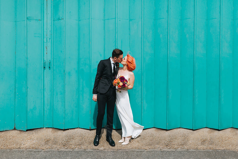 bride with pink hair with groom in front of turquoise door in East London by modern london wedding photographer miss gen