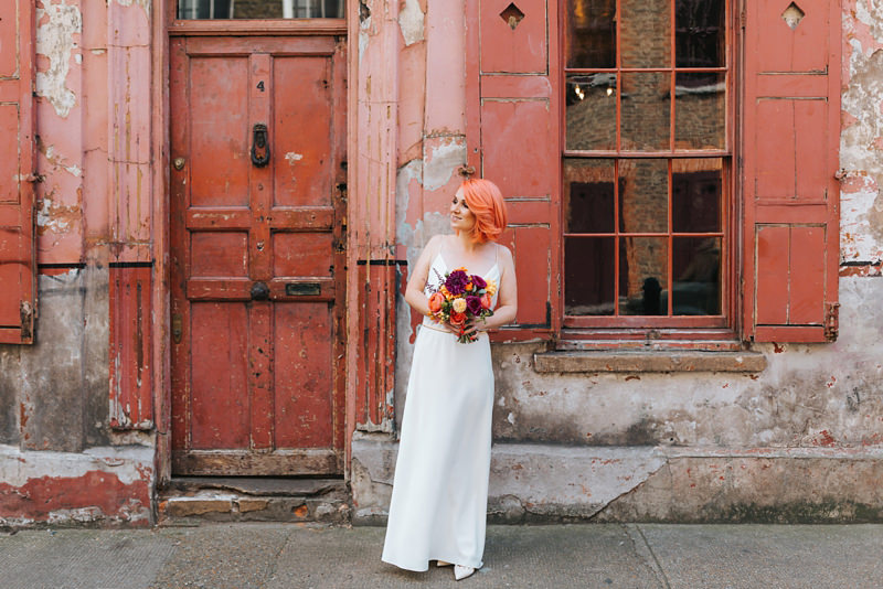 bride with pink hair in front of pink building by destination wedding photographer miss gen