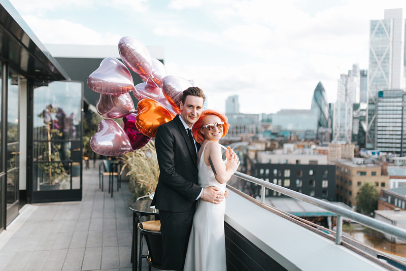 Ace Hotel London Rooftop Wedding Bride And Groom Holding Bunch Of Helium Balloons