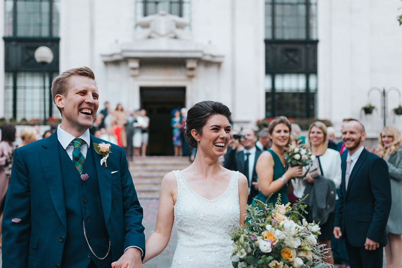 happy married couple outside Islington Town Hall by relaxed natural destination wedding photographer miss gen