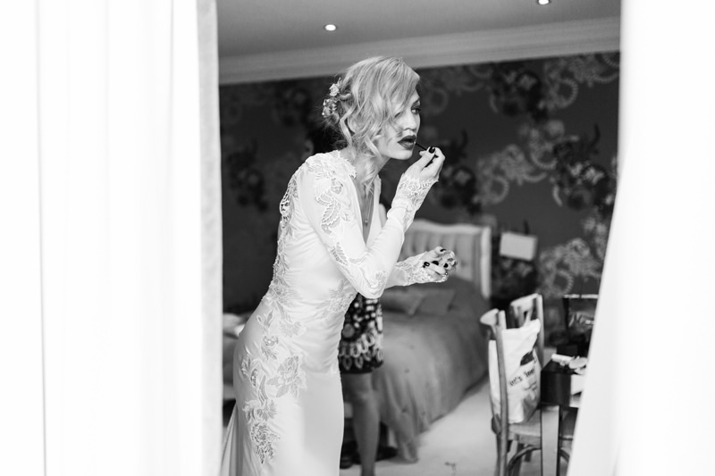 bride applying lipstick in inbal dror by relaxed london wedding photographer missgen