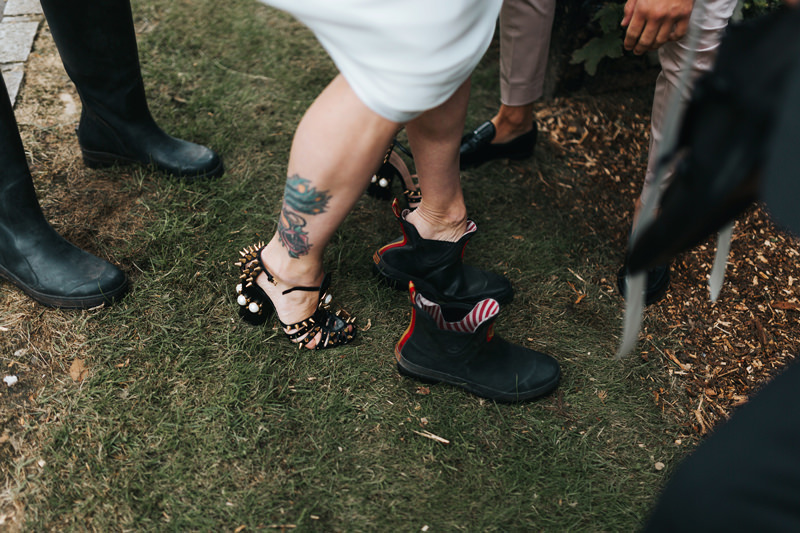 bride in wellies and gucci spiked heels by relaxed natural wedding photographer miss gen