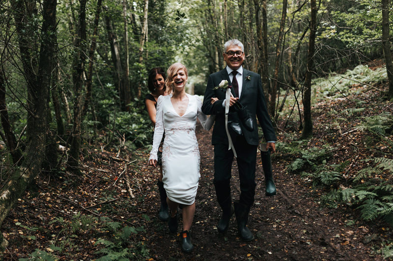 bride walking with dad through kent woodland by destination wedding photographer miss gen