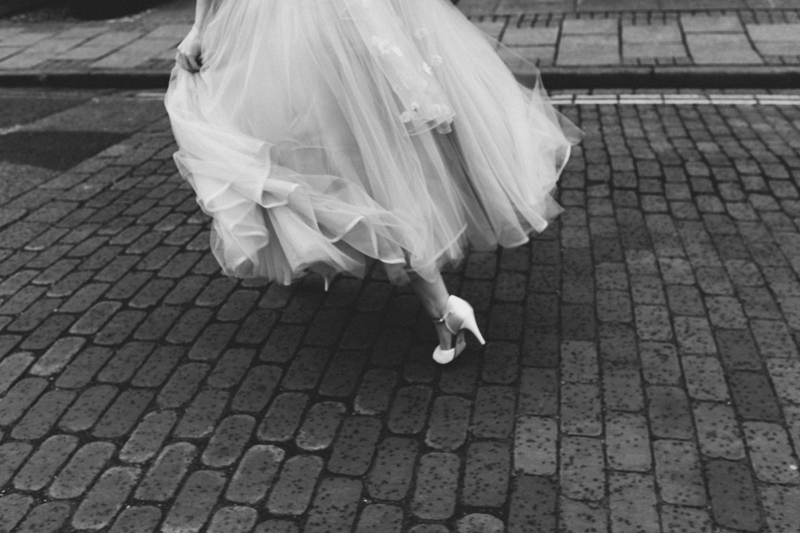 brides dress and shoe running across road in the rain, creative documenary wedding photogrpaphy by contemporary london wedding photographer miss gen