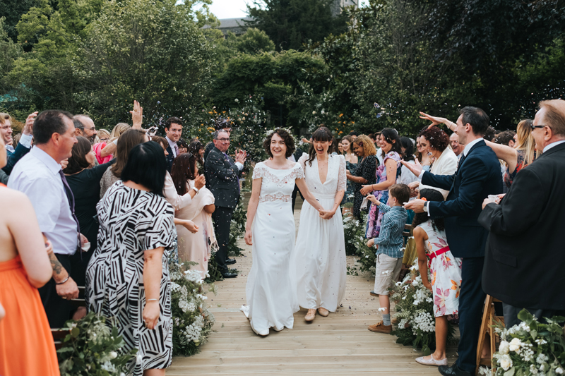 two brides walking down aisle with confetti, outdoor wedding by alternative wedding photographer miss gen