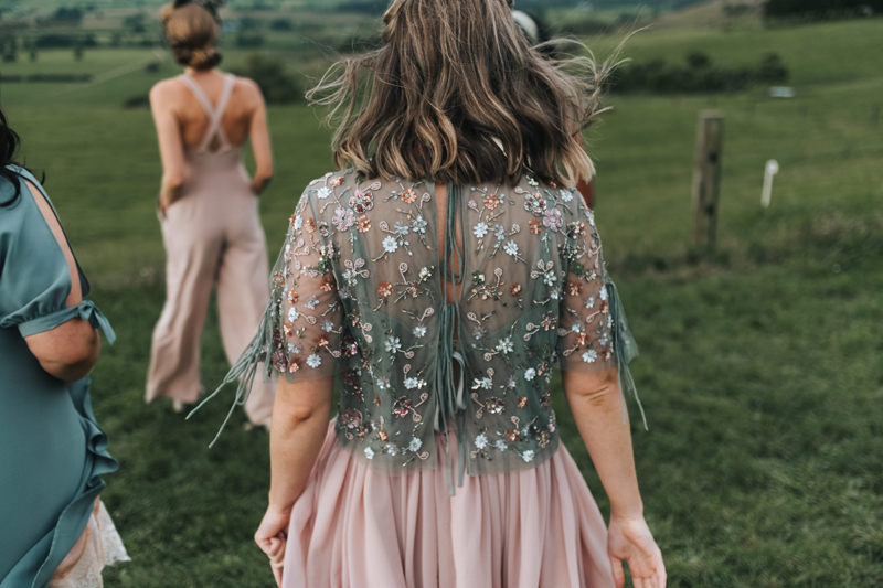bridesmaids wearing mismatched blush dresses & jumpsuits walking in the countryside of New Zealand