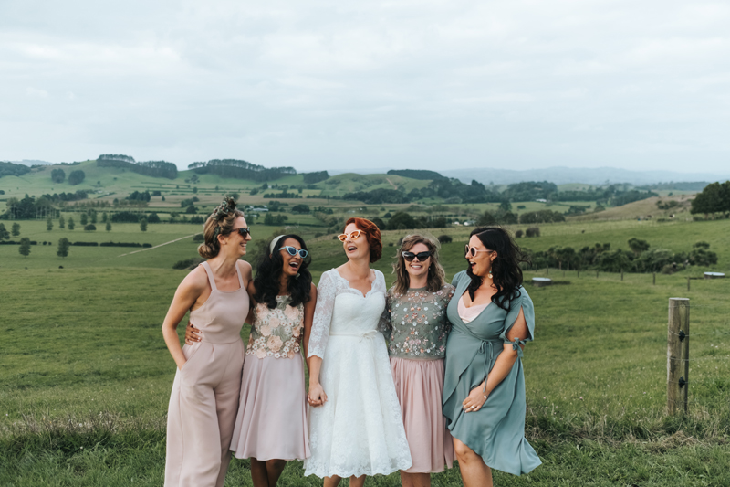 bridesmaids wearing mismatched blush dresses & jumpsuits & 1950s sunglasses in the countryside of New Zealand