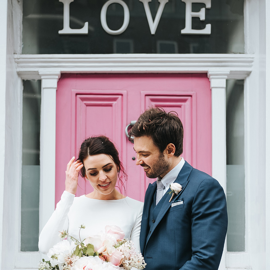 relaxed, modern bride & groom portrait in front of pink door in chelsea, London