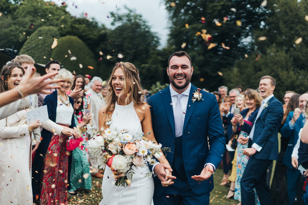 bride and groom walking through confetti outside in a field by londonmodern wedding photographer miss gen